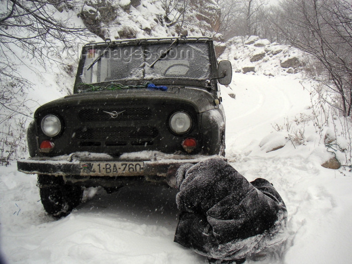 azer160: Azerbaijan - outside Quba: snow chains being put on a UAZ jeep - road to to Xiniliq (photo by Austin Kilroy) - (c) Travel-Images.com - Stock Photography agency - Image Bank