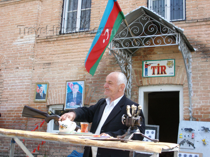 azer442: Sheki / Shaki - Azerbaijan: man recruiting for target practice - Azeri flag and the Aliyevs in the background - photo by N.Mahmudova - (c) Travel-Images.com - Stock Photography agency - Image Bank