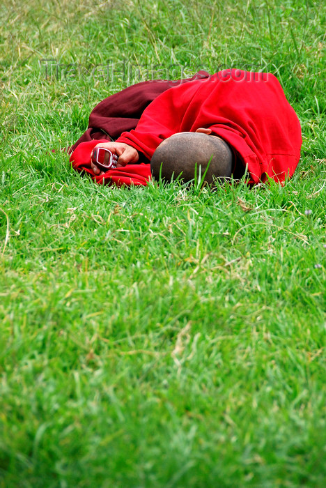 bhutan406: Bhutan, Paro, Monk on grass outside Paro Dzong with cellphone - photo by J.Pemberton - (c) Travel-Images.com - Stock Photography agency - Image Bank