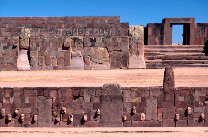 bolivia131: Tiwanaku / Tiahuanacu, Ingavi Province, La Paz Department, Bolivia: Semi-Underground Temple with carved enemy heads – Kalasasaya temple gate in the background - photo by C.Lovell - (c) Travel-Images.com - Stock Photography agency - Image Bank