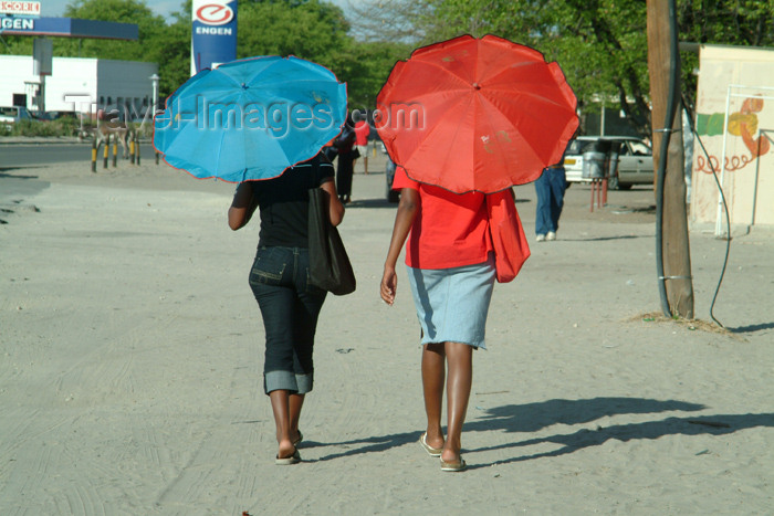 botswana15: Maun, North-West District, Botswana: covering from the sun - two women walk with umbrellas - photo by J.Banks - (c) Travel-Images.com - Stock Photography agency - Image Bank