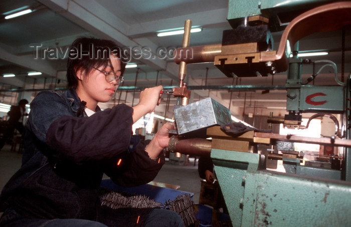 china250: Dongguan, Guangdong province, China: metal worker operating a machine - Chinese factory worker - photo by B.Henry - (c) Travel-Images.com - Stock Photography agency - Image Bank
