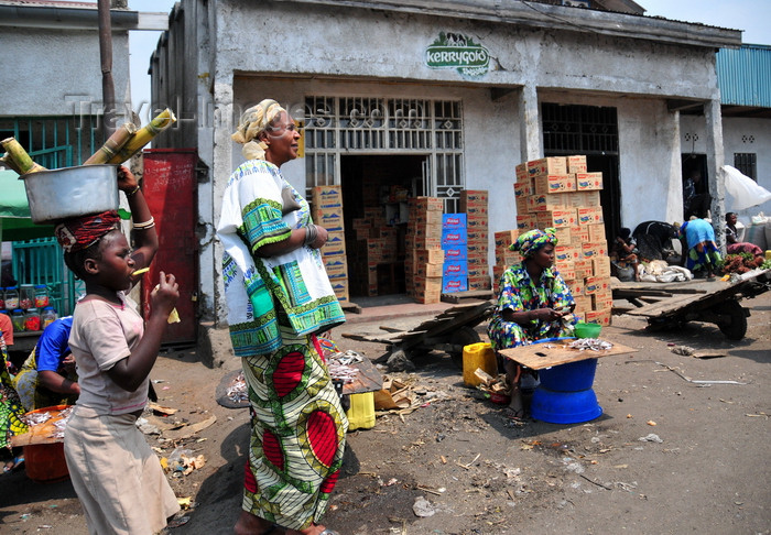 congo-dr5: Goma, Nord-Kivu, Democratic Republic of the Congo: street scene - commerce - woman in traditional clothes and girl with sugar cane - Kerrygold logo - piles of Rwenzori and Riham power boxes - photo by M.Torres - (c) Travel-Images.com - Stock Photography agency - Image Bank