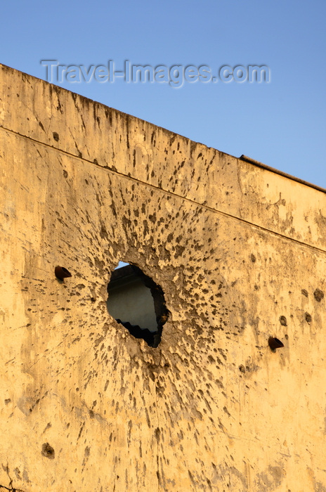 congo32: Brazzaville, Congo: war damage - impact of an RPG on the wall of a colonial building, a few bullet holes are also included, for good measure - Avenue Amilcar Cabral, Quartier de la Plaine - photo by M.Torres - (c) Travel-Images.com - Stock Photography agency - Image Bank