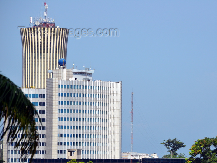 congo64: Brazzaville, Congo: building of the National Petroleum Company of the Congo, SNPC, Société nationale des pétroles du Congo - in the background the Nabemba tower / Elf Tower - palm tree leaf in the foreground - photo by M.Torres - (c) Travel-Images.com - Stock Photography agency - Image Bank