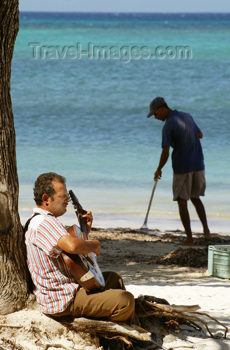 cuba34: Cuba - Guardalavaca - beach - playing guitar and sweeping - photo by G.Friedman - (c) Travel-Images.com - Stock Photography agency - Image Bank