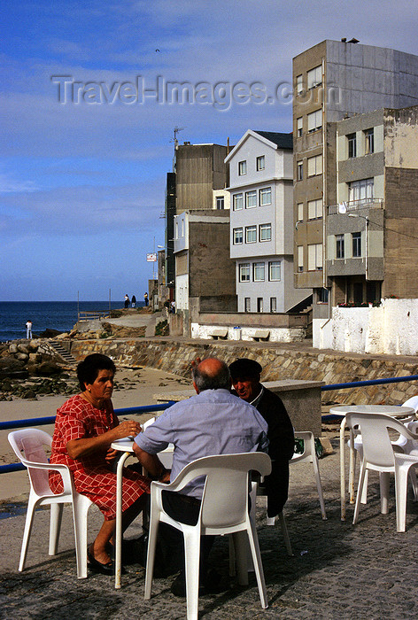 galicia59: Galicia / Galiza - Malpica de Bergantiños - A Coruña province: people at a pavement café by the beach - Costa da Morte - photo by S.Dona' - (c) Travel-Images.com - Stock Photography agency - Image Bank