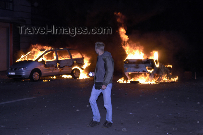 germany282: Germany - Berlin: riots on May 1st - pedestrian passes burning cars - photo by W.Schmidt - (c) Travel-Images.com - Stock Photography agency - Image Bank