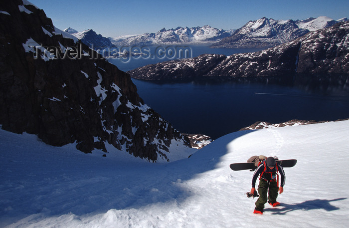 greenland87: Greenland, Apussuit: snowboarder with heavy load climbing steep snow slope - photo by S.Egeberg - (c) Travel-Images.com - Stock Photography agency - Image Bank