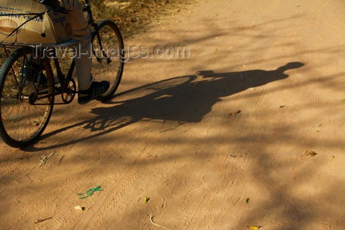 guinea-bissau166: Praia de Varela / Varela beach, Cacheu region, Guinea Bissau / Guiné Bissau: Shadow of a man riding a bycicle, everyday life / Sombra de um homem a andar de bicicleta, casa tradicional, vida quotidiana - photo by R.V.Lopes - (c) Travel-Images.com - Stock Photography agency - Image Bank