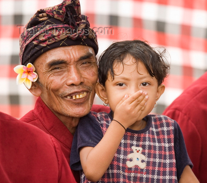 indonesia124: Padangbai, Bali, Indonesia: toddler and musician with frangipani and turban - photo by D.Smith - (c) Travel-Images.com - Stock Photography agency - Image Bank