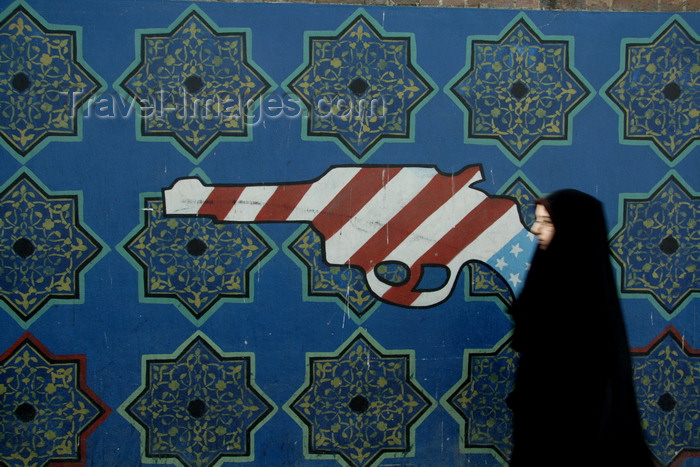 iran570: Tehran, Iran: propaganda - Graffiti at the former US embassy - psychedelic gun and woman in chador - photo by G.Koelman - (c) Travel-Images.com - Stock Photography agency - Image Bank