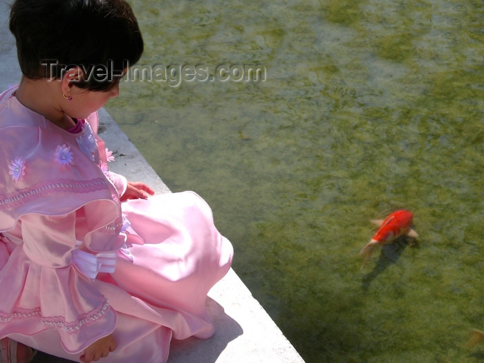 israel392: Israel: small girl dressed-up for the Purim celebrations, watching the fish in a pond - photo by E.Keren - (c) Travel-Images.com - Stock Photography agency - Image Bank