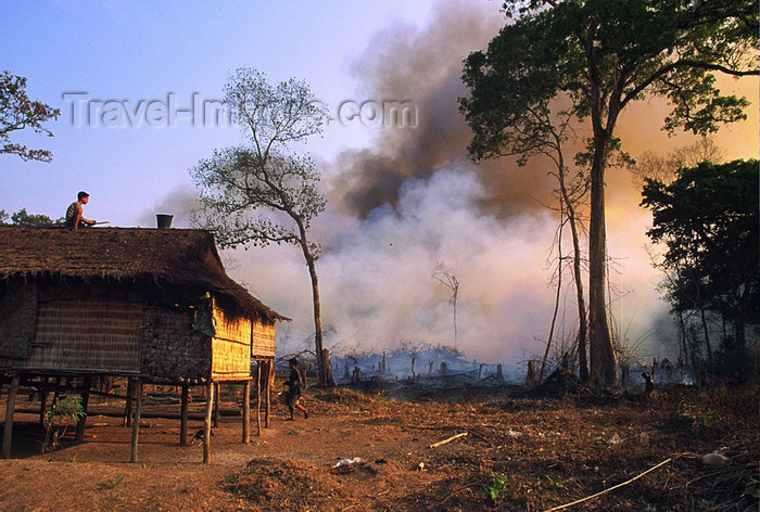 laos102: Laos: forest fire - a man is on the roof of his house with a bucket of water against the fire  - photo by E.Petitalot - (c) Travel-Images.com - Stock Photography agency - Image Bank