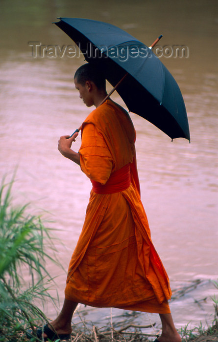 laos57: Laos - Luang Prabang / Louangphrabang - Monk with umbrella walks along the Mekong River (photo by K.Strobel) - (c) Travel-Images.com - Stock Photography agency - Image Bank