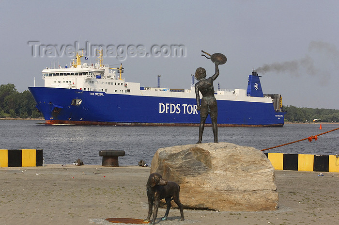 lithuania206: Klaipeda, Lithuania: bronze sculpture of a boy and dog meeting ships - a ferry enters the harbour - Tor Maxima - photo by A.Dnieprowsky - (c) Travel-Images.com - Stock Photography agency - Image Bank