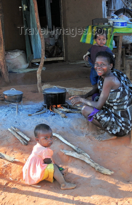 madagascar244: West coast road between the Manambolo river and Belon'i Tsiribihina, Toliara Province, Madagascar: Sakalava woman and her two daughters - cooking a meal outside the house - photo by M.Torres - (c) Travel-Images.com - Stock Photography agency - Image Bank