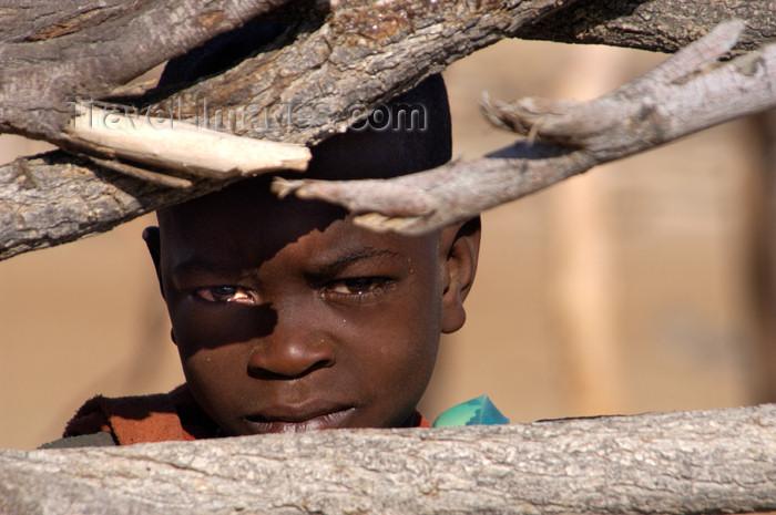 namibia144: Namibia: Himba Boy peering through fence, Skeleton Coast, Kunene region - photo by B.Cain - (c) Travel-Images.com - Stock Photography agency - Image Bank