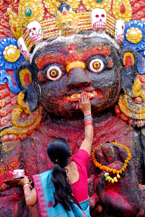 nepal216: Kathmandu, Nepal: woman making a food offer to Kala Bhairava, ferocious manifestation of Shiva associated with annihilation - Hanuman Dhoka, Durbar square - photo by J.Pemberton - (c) Travel-Images.com - Stock Photography agency - Image Bank