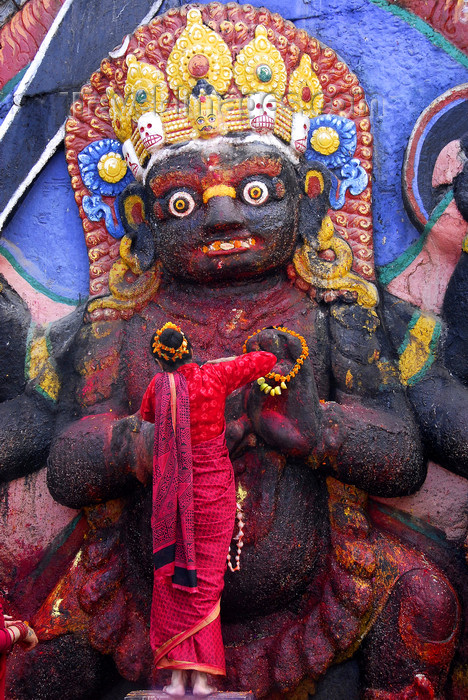nepal217: Kathmandu, Nepal: woman making offering to Kala Bhairab statue in Durbar square - 17th century stone image - photo by J.Pemberton - (c) Travel-Images.com - Stock Photography agency - Image Bank