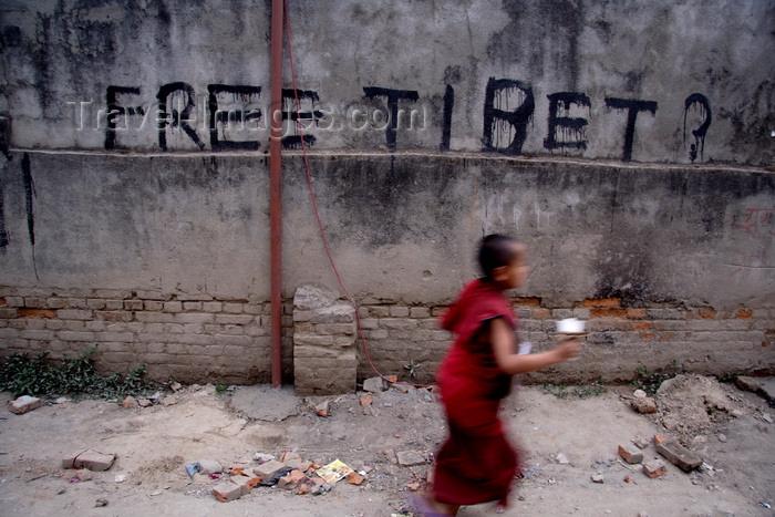 nepal4: Kathmandu, Nepal: 'Free Tibet' graffiti and passing Tibetan monk - photo by G.Koelman - (c) Travel-Images.com - Stock Photography agency - Image Bank