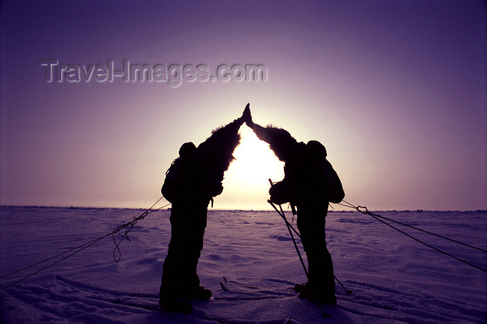north-pole2: North Pole: celebrating a successful expedition - silhouettes and sun in the North Pole - two skiers - Severní pól, Nordpolen,Polo Norte, Pôle Nord, Polo Nord, Noordpool, Polul Nord (photo by Eric Philips) - (c) Travel-Images.com - Stock Photography agency - Image Bank