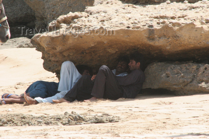 pakistan76: Karachi, Sindh, Pakistan: men resting under rocks - while waiting for customers at the French Beach - the shade - photo by R.Zafar - (c) Travel-Images.com - Stock Photography agency - Image Bank