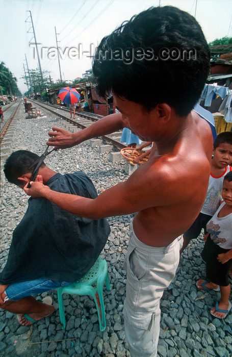 phil24: Manila city, Philippines - haircut on the railway tracks - Slums and shanty towns - photo by B.Henry - (c) Travel-Images.com - Stock Photography agency - Image Bank