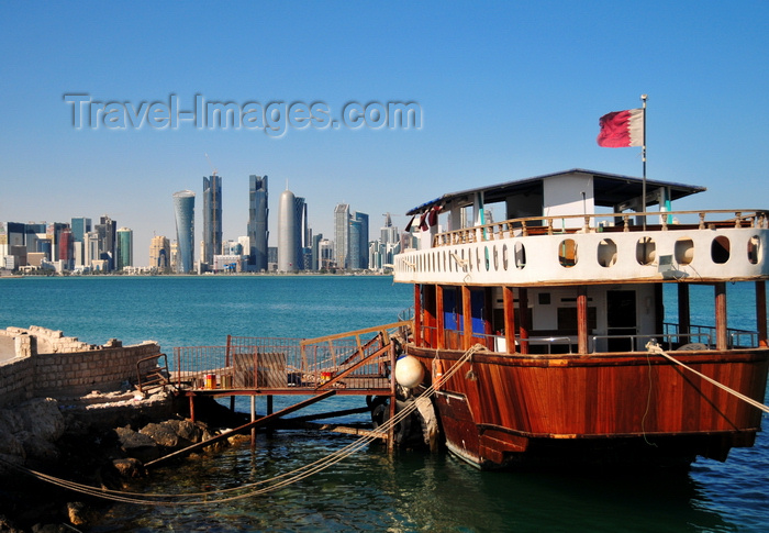 qatar50: Doha, Qatar: old boat with Qatari flag in the Dhow harbour - West Bay skyline from the south side of Doha Bay - photo by M.Torres - (c) Travel-Images.com - Stock Photography agency - Image Bank