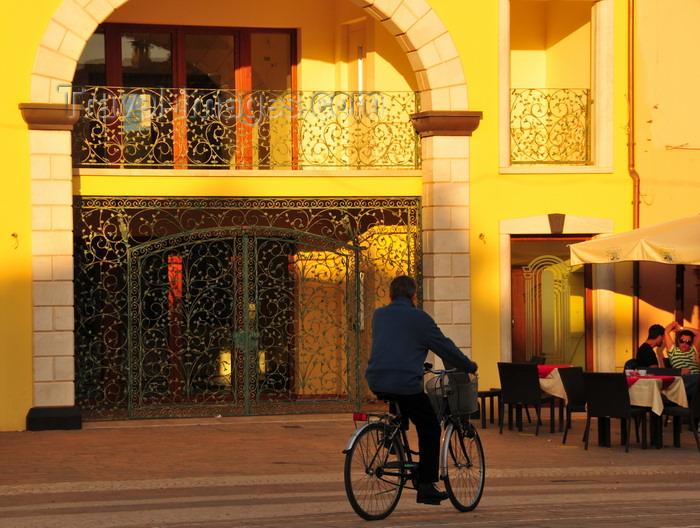 sardinia245: Pula, Cagliari province, Sardinia / Sardegna / Sardigna: cyclist and elaborate iron gate - Piazza del Popolo - Via Nora - photo by M.Torres - (c) Travel-Images.com - Stock Photography agency - Image Bank