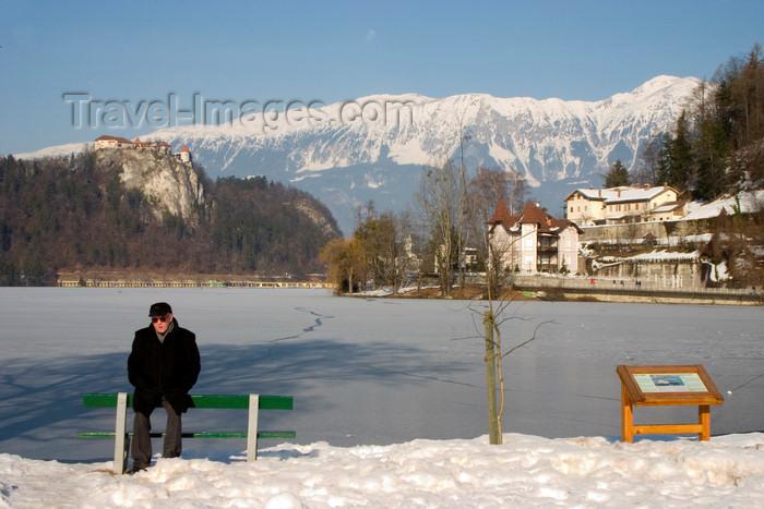 slovenia179: Slovenia - men on bench - view across Lake Bled in Slovenia when frozen over in winter - Karavanke mountain range - photo by I.Middleton - (c) Travel-Images.com - Stock Photography agency - Image Bank