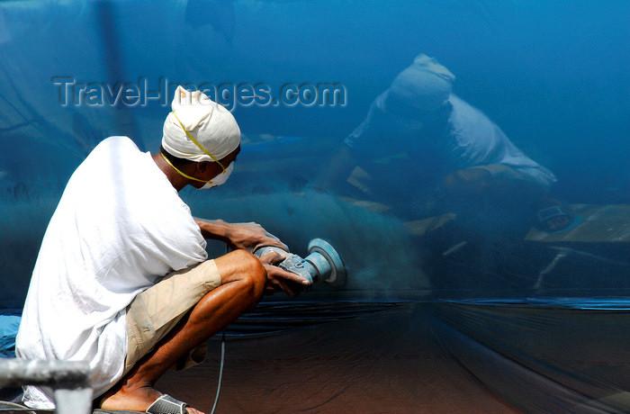 trinidad-tobago51: Port of Spain, Trinidad: worker polishing the hull of a sailing boat - photo by E.Petitalot - (c) Travel-Images.com - Stock Photography agency - Image Bank