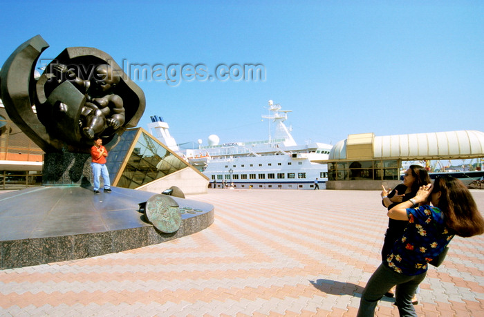 ukra35: Odessa, Ukraine: woman taking picture of man standing at a statue of a hatching baby, called the 'Golden boy' by sculptor Ernst Neizvestny - Maritime Terminal area - cruise ship Arkona in the dock - photo by K.Gapys - (c) Travel-Images.com - Stock Photography agency - Image Bank