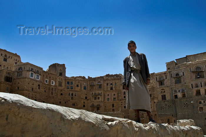 yemen105: Hababah, Sana'a governorate, Yemen: young man standing on wall in front of Old Town buildings - photo by J.Pemberton - (c) Travel-Images.com - Stock Photography agency - Image Bank