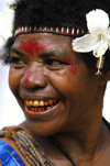 PNG - Papua New Guinea - Colorful woman with white hibiscus, Tuam Island, Dampier Strait, Morobe province - photo by B.Cain