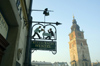 Poland - Krakow: restaurant sign and Town Hall tower - photo by M.Gunselman