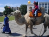 Russia - Kyzyl (Tuva / Tyva republic): children riding a Bactrian camel  in the central square (photo by A.Kilroy)