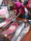 Chechnya, Russia - Grozny - fishmonger stall - Chechen woman cuts the fish in market - photo by A.Bley