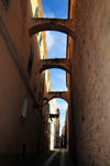 Alghero / L'Alguer, Sassari province, Sardinia / Sardegna / Sardigna: narrow street with arches - counter-thrust bows - photo by M.Torres