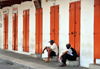 Mahe, Seychelles: idle time on Market street - men and red doors - photo by M.Torres