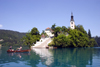Slovenia - Couple rowing past church of the Assumption on Lake Bled - photo by I.Middleton