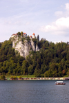 Slovenia - Gondolier rowing tourists across Lake Bled with castle on cliff in background - photo by I.Middleton