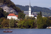 Slovenia - Gondolier rowing tourists across Lake Bled with Bled church in background - photo by I.Middleton
