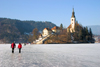 Slovenia - people walking across ice - island church on Lake Bled in Slovenia when frozen over in winter - photo by I.Middleton