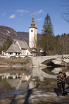 Slovenia - Ribcev Laz - couple, St John's church and bridge - Bohinj Lake in Spring - photo by I.Middleton