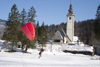 Slovenia - Ribcev Laz - man preparing to paraglide across a frozen Bohinj Lake - St John's church in the background - photo by I.Middleton