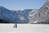 Slovenia - Couple walking across Bohinj Lake / Wocheinersee when frozen over - view towards Ukanc - photo by I.Middleton