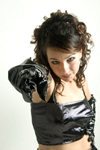 Young woman in a glamorous fashion pose wearing a black vinyl dress and black gloves while pointing at the camera with a threatening look - photo by D.Smith