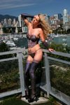 Young woman wearing painted on lingerie outdoors with Vancouver skyline in background. Model Paige Monroe. Model released - photo by D.Smith