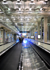 Bang Phli District, Samut Prakan Province, Thailand: Suvarnabhumi Airport, aka as New Bangkok International Airport - people on moving walkway in an industrial architecture environment - vanishing point - photo by M.Torres